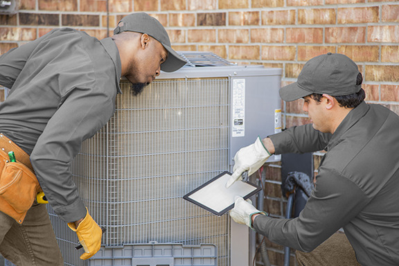 Two techs performing maintenance on an outdoor AC unit