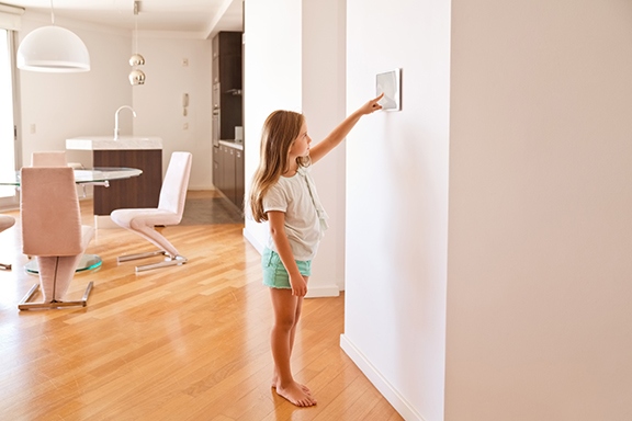 A girl changing the thermostat