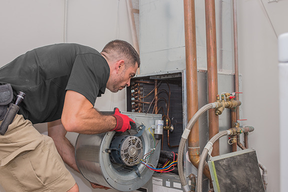 A tech installing a blower in a furnace