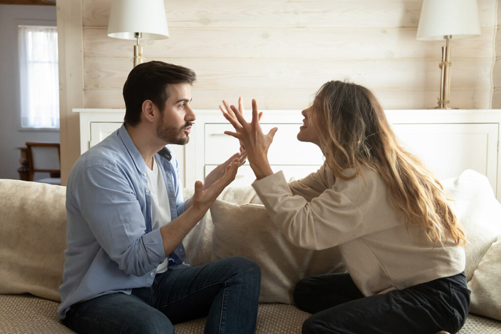 A man and a woman arguing in a bedroom