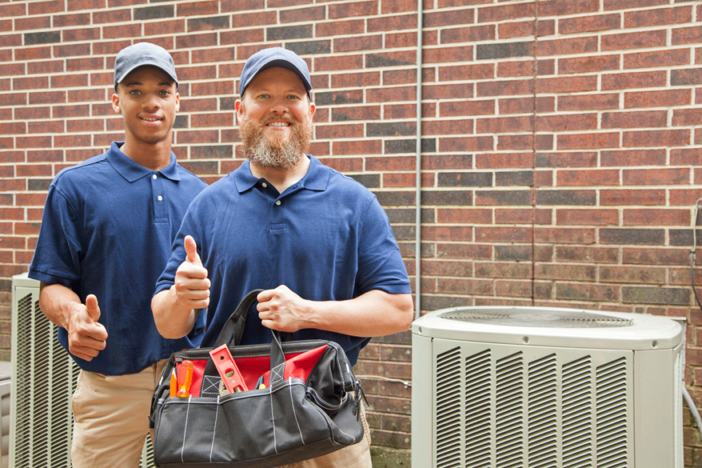 A pair of technicians giving a thumbs up next to an outdoor A/C unit
